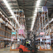 warehouse with forklift being driven around shelves of goods