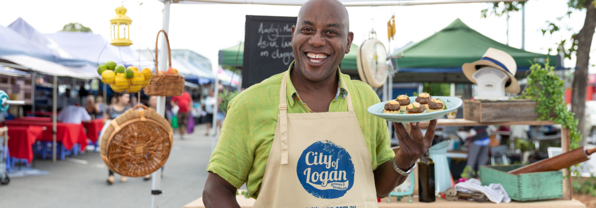 Chef Ainsley smiling and holding a plate of food