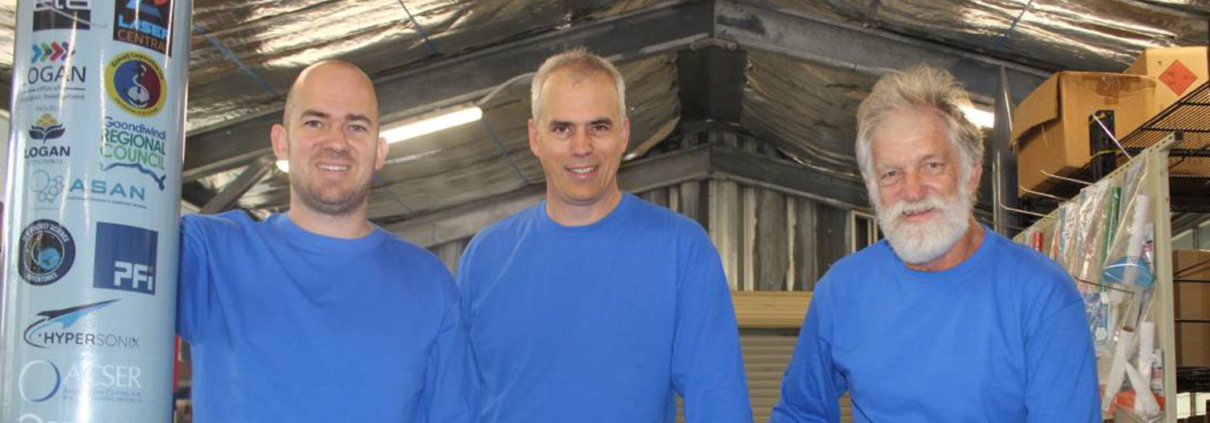 Three employees of Black Sky Aerospace standing together and smiling