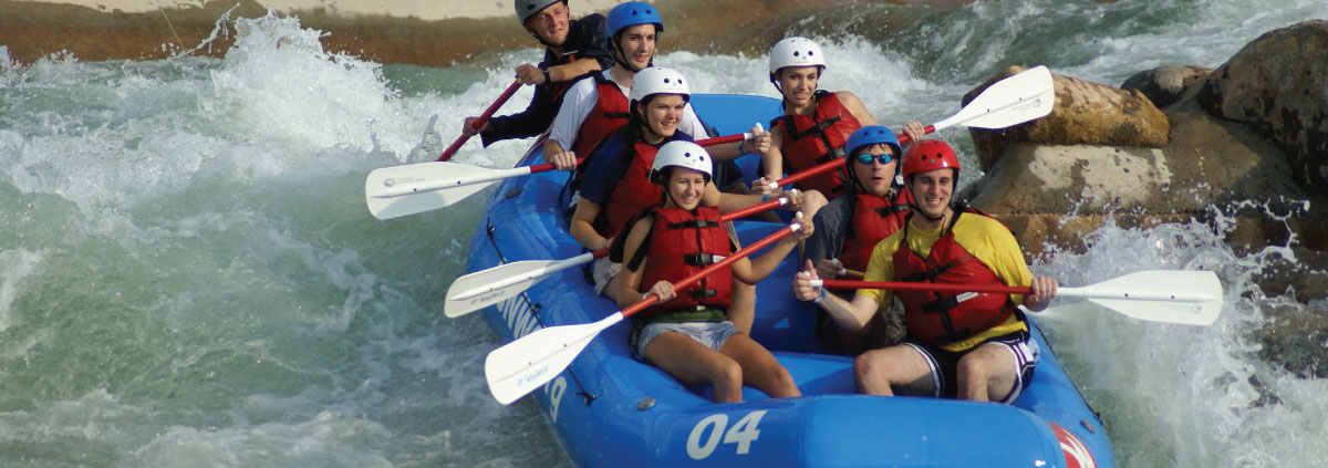 Seven people in whitewater raft paddling down rapids