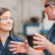 Two factory workers smiling and chatting