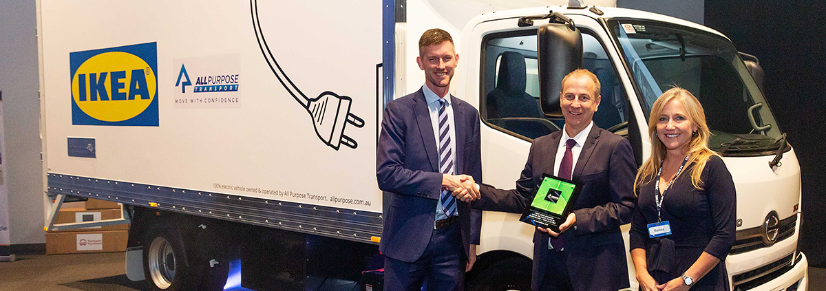 Woman smiling and two men shaking hands in front of a IKEA truck