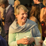 Smiling women having a conversation in a crowd of people