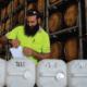 Man putting labels on sanitiser bottles in rum barrel warehouse