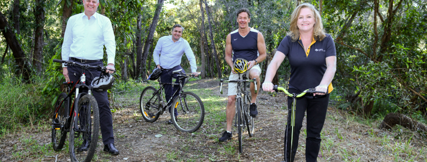 This is a picture of four people at the the location of the future rail trail.