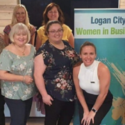 woman standing in front of 'Logan City Women in Business' banner
