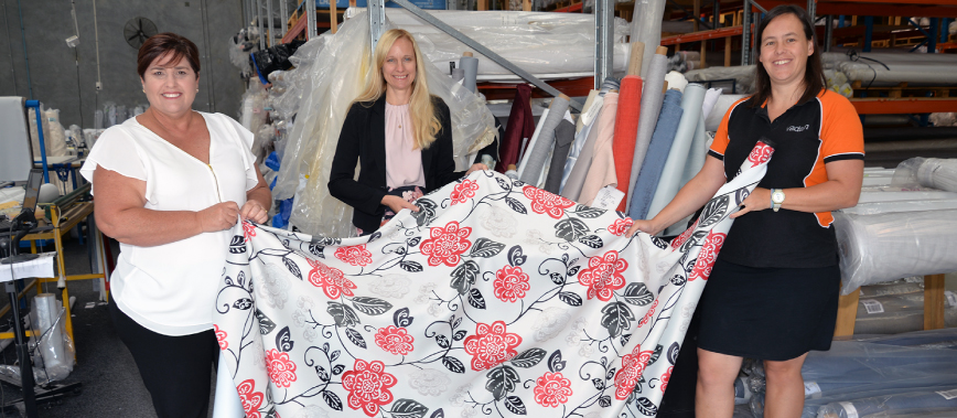 Councillors Murphy and Stemp holding a bolt of fabric with Tessa Schouten from Vadain