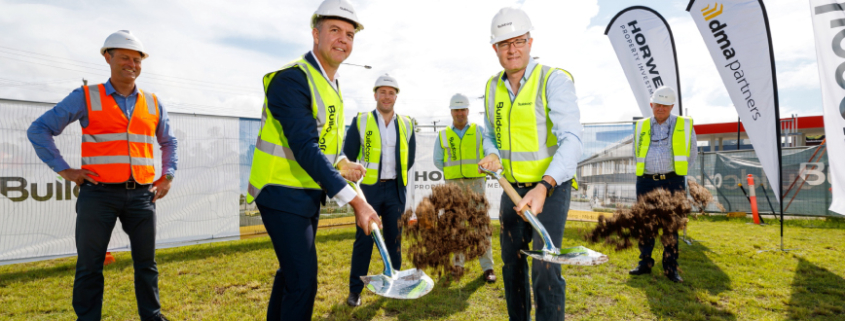 Contractor staff turning sod at future construction site