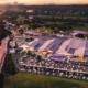 Aerial photo of Distillery Road Market next to motorway, with artist render of markets