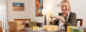 Woman at dining table holding product - a home-based business